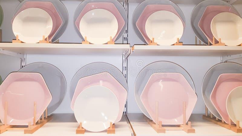Platos de cer?mica de las placas blancos y rosados en grandes almacenes de los estantes de la tienda imagenes de archivo
