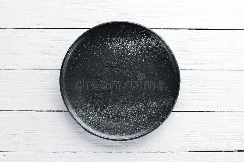 Platos de la arcilla Una placa en un fondo de madera blanco fotografía de archivo