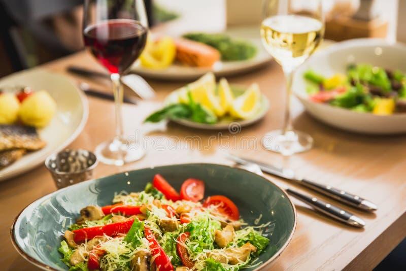 Platos de la ensalada en una placa y un vidrio de vino Comida sana en café imagen de archivo