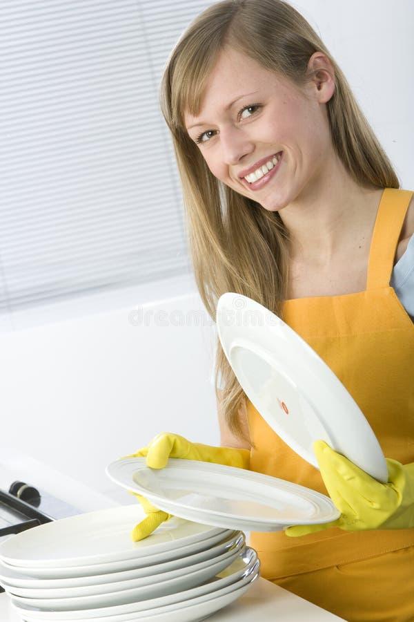 Platos de la limpieza de la mujer foto de archivo