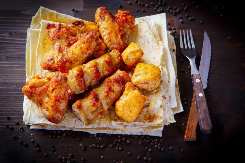 Platos de la parrilla, kebab para el menú del restaurante Fondo de madera Carnes y pan Pita del pollo imagen de archivo