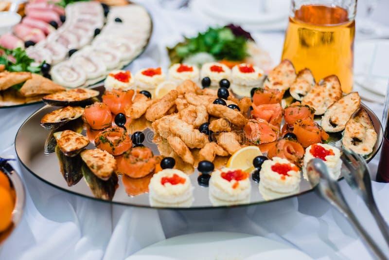 Platos de pescados de salmones, de mejillones y del caviar en una placa foto de archivo libre de regalías