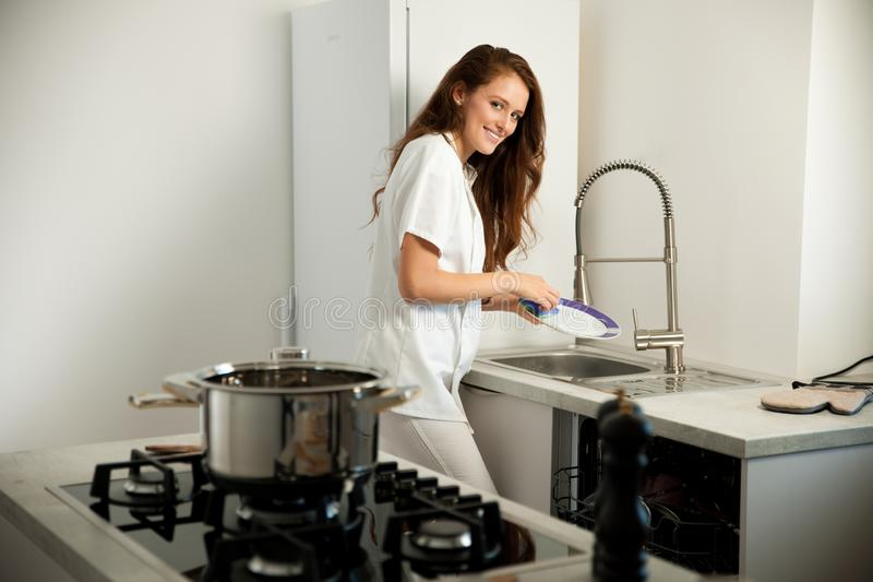 Platos hermosos del lavado de la mujer joven en el kictchen foto de archivo
