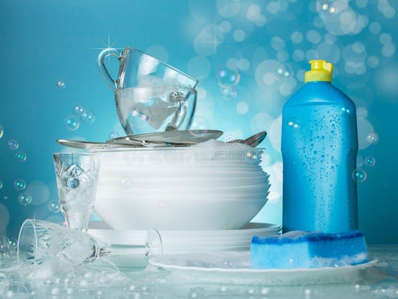 Platos lavados limpios, lavaplatos y burbujas de jabón en azul foto de archivo libre de regalías