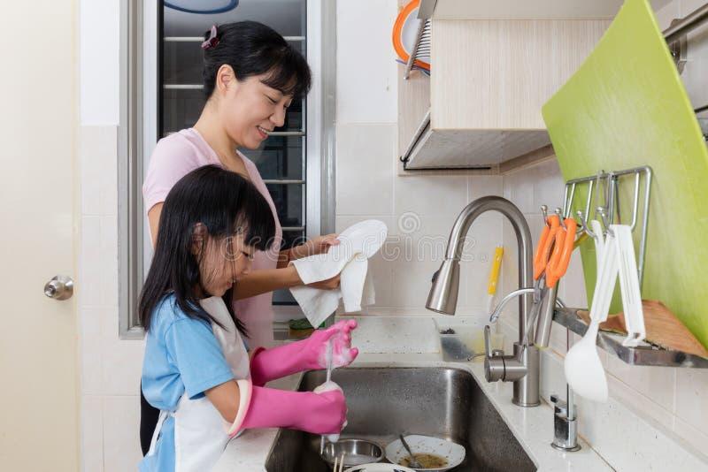 Platos que se lavan de ayuda de la madre de la niña china asiática imagenes de archivo