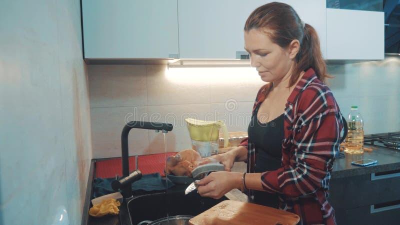 Platos que se lavan de la muchacha en la tabla de cortar de la cocina Cocineros de la mujer en la cocina la muchacha lava un cuch imagen de archivo