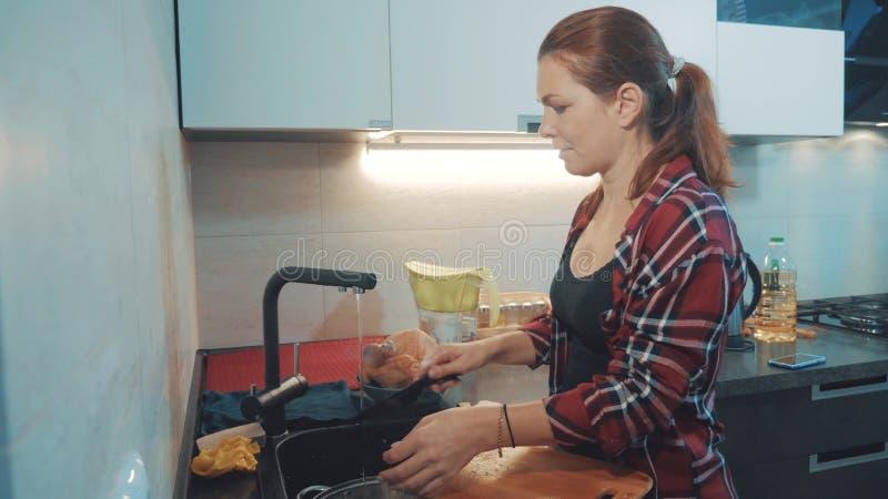 Platos que se lavan de la muchacha en la tabla de cortar de la cocina Cocineros de la mujer en la cocina la muchacha lava un cuch imagenes de archivo