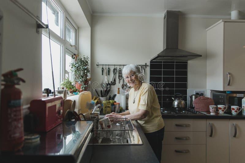 Platos que se lavan de la mujer mayor feliz imagen de archivo libre de regalías
