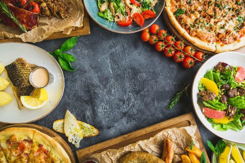 Platos sabrosos en la tabla oscura Costillas de cerdo, pizza, ensaladas, pescados y salchichas asados a la parrilla con las patat imagenes de archivo