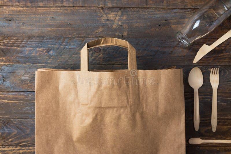 Platos y cubiertos de madera del bolso de compras del papel de Brown Kraft en el fondo de madera basura cero de las alternativas  fotos de archivo
