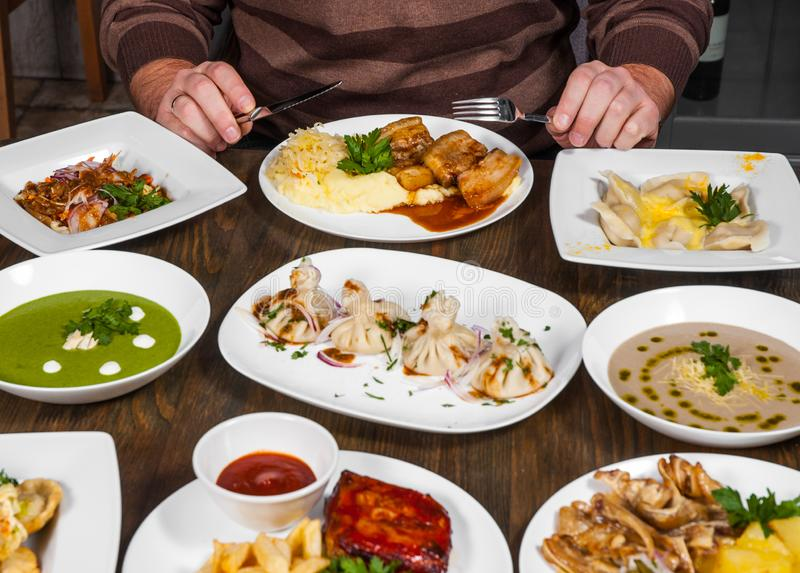 Plats avec différentes mains de foodman avec un couteau et une fourchette à la table avec des beaucoup nourriture différente image stock