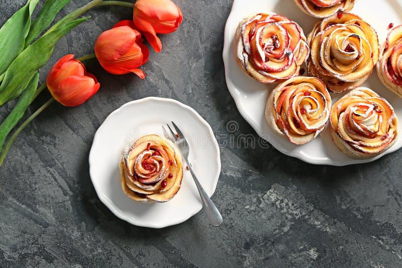 Plats avec la pâtisserie formée rose savoureuse de pomme sur la table image stock