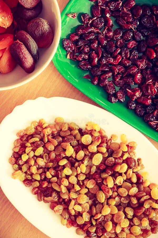 Plats avec les canneberges, les abricots et les raisins secs secs photos stock