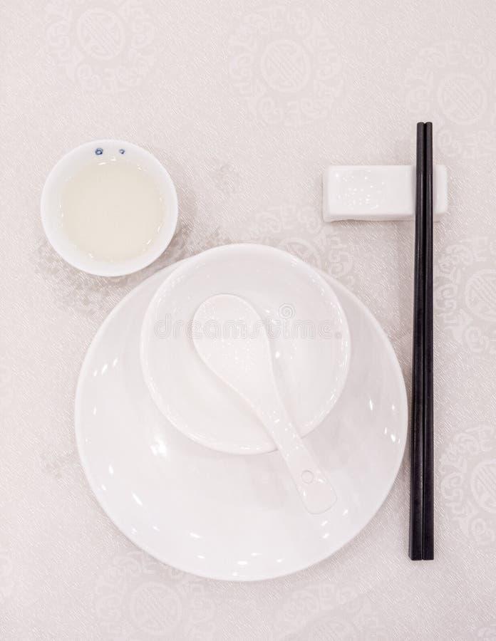 Plats blancs dans un restaurant chinois aux baguettes noires photo libre de droits