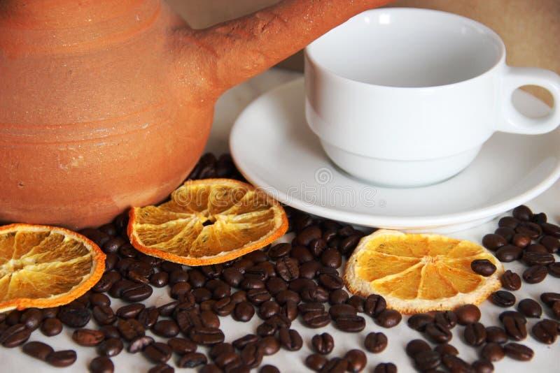 plats bruns d'argile, tasse et soucoupe propre blanche, grains de café rôtis et orange sèche sur la table grise photos libres de droits