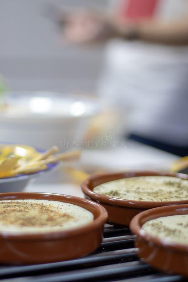 Plats d'argile avec du fromage de provolone avec des herbes pour le gratin image libre de droits