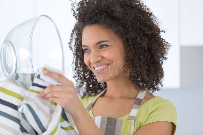 Plats de lavage de belle jeune femme au foyer avec l'éponge photographie stock