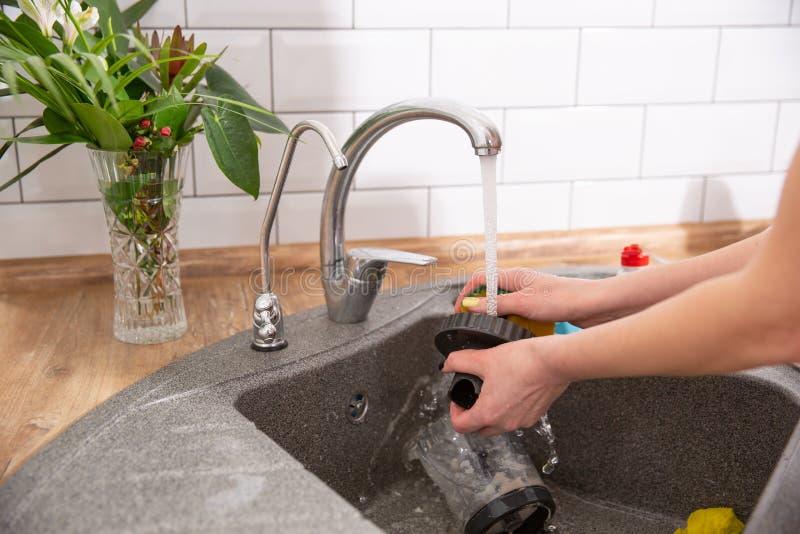 Plats de lavage de femme dans la cuisine Fermez-vous de la main de femme image libre de droits