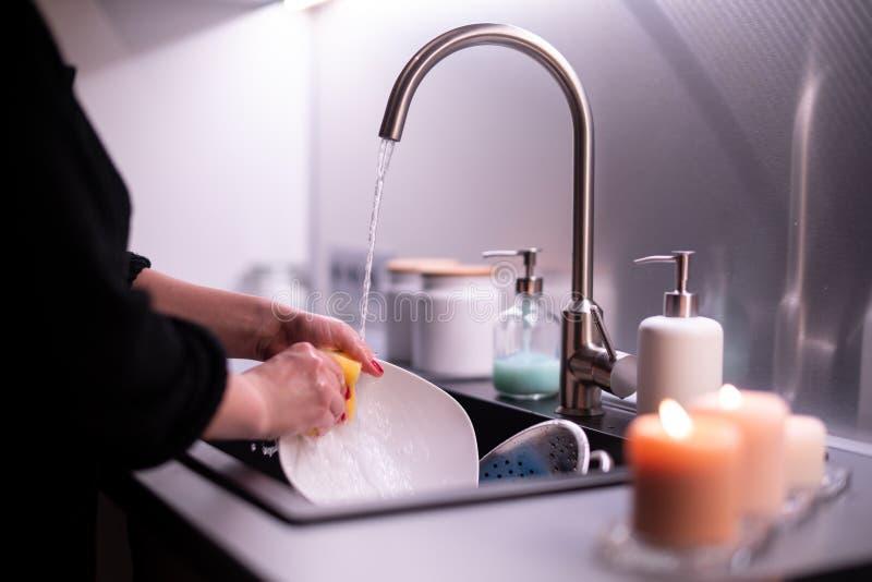 Plats de lavage de jeune femme à la maison photo stock
