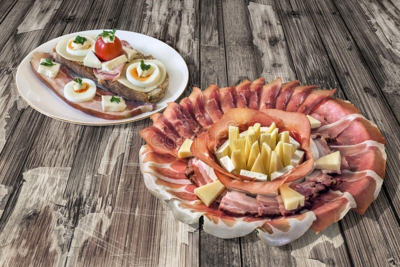 Plats de plat savoureux d'apéritif avec l'ensemble de sandwich à fromage et à tomate d'oeufs de lard sur le vieux Tableau floconn image stock