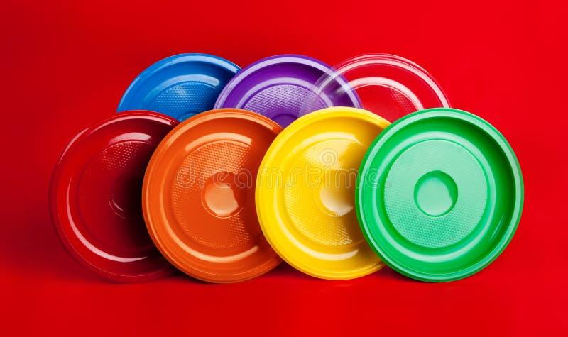 Plats en plastique colorés sur le fond rouge photos libres de droits