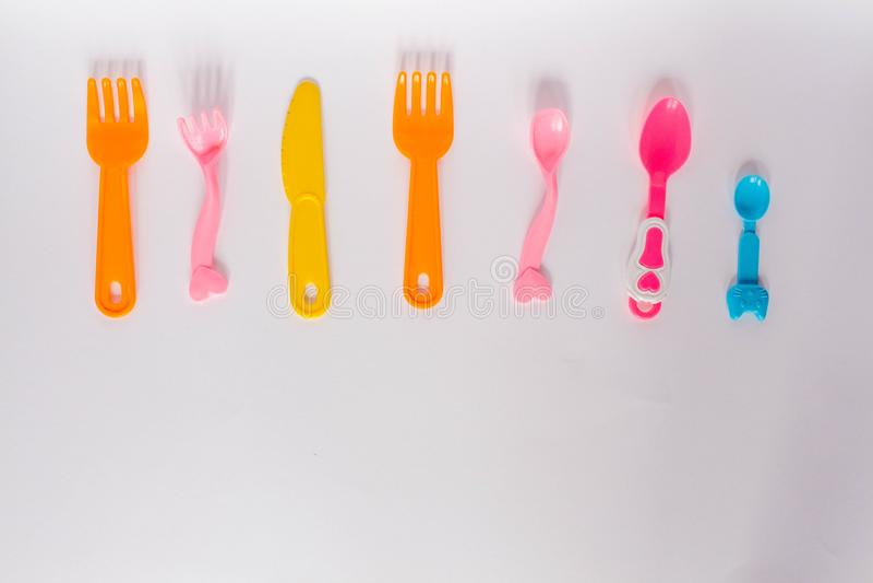 Plats en plastique d'enfants sur un fond blanc, fourchettes, cuillères, plat avec l'espace pour le texte Configuration plate, con illustration stock