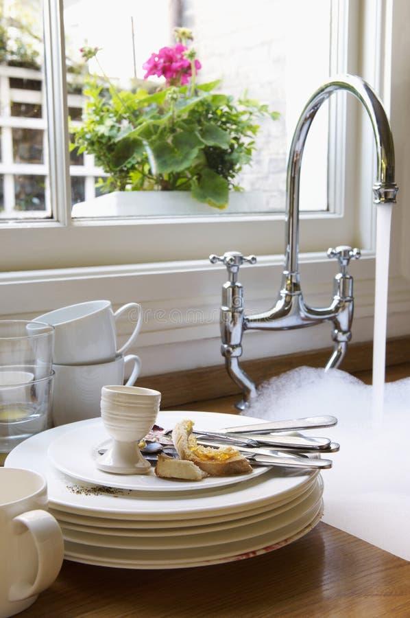 Plats et argenterie sales par l'évier avec l'eau courante photographie stock