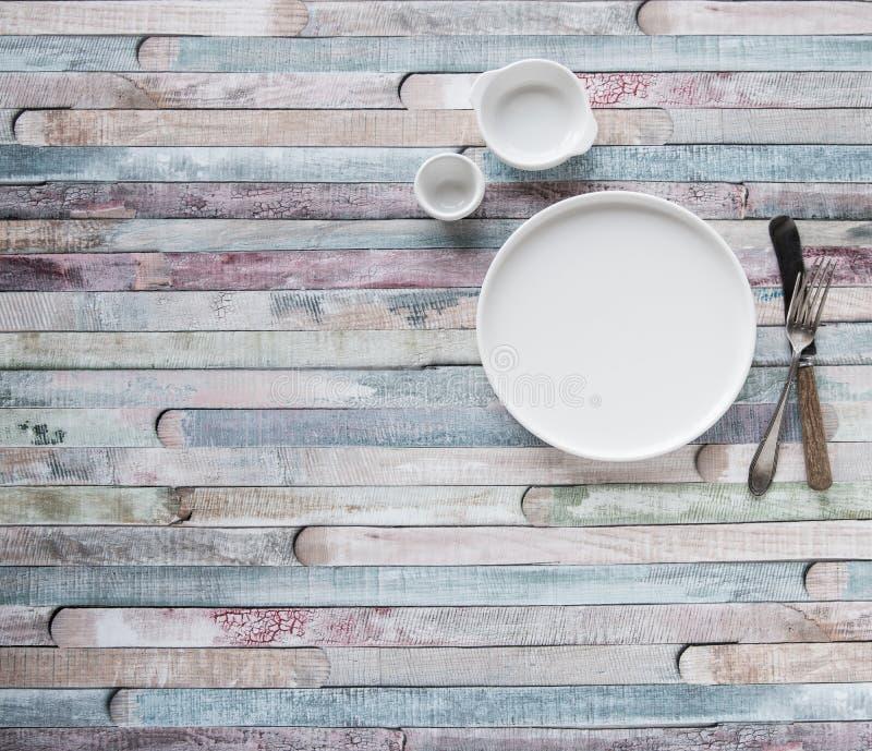 Plats et cuillères et fourchette blancs de cru sur le fond en bois de couleur images libres de droits