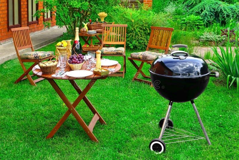 Plats för BBQ-familjparti i dekorativ trädgård på trädgården arkivfoto