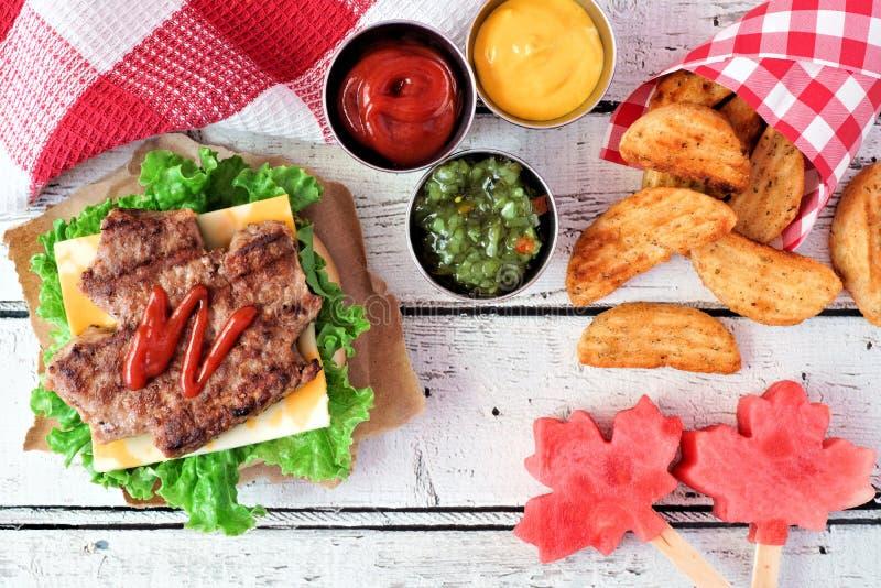 Plats för Kanada dagpicknick med den lönnlövhamburgaren och vattenmelon royaltyfri foto