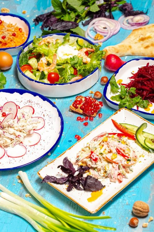 Plats géorgiens aux herbes, viandes, légumes hachés et épices sur 5 assiettes blanches, sur fond de mer bleue images stock
