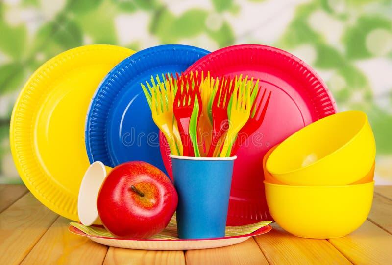Plats jetables lumineux, tasses, cuvettes en plastique, fourchettes sur le vert abstrait photographie stock