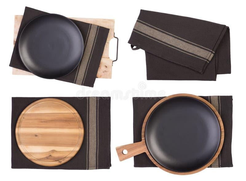 Plats noirs, planches à découper et serviettes de thé d'isolement sur le fond blanc, vue supérieure photos stock