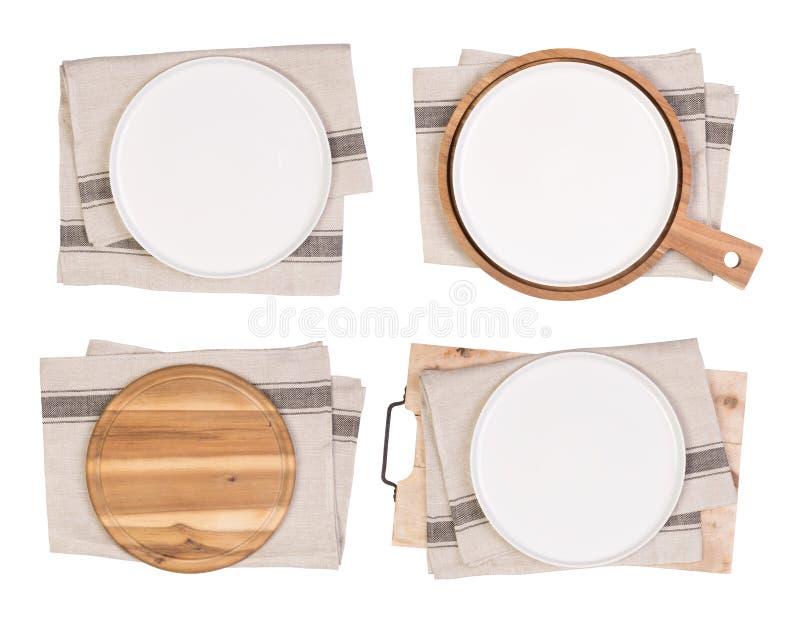 Plats, planches à découper blanches et serviettes de thé d'isolement sur le fond blanc images libres de droits