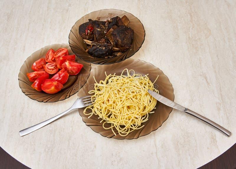 Plats sur la table avec de la viande frite, pâtes et photos libres de droits