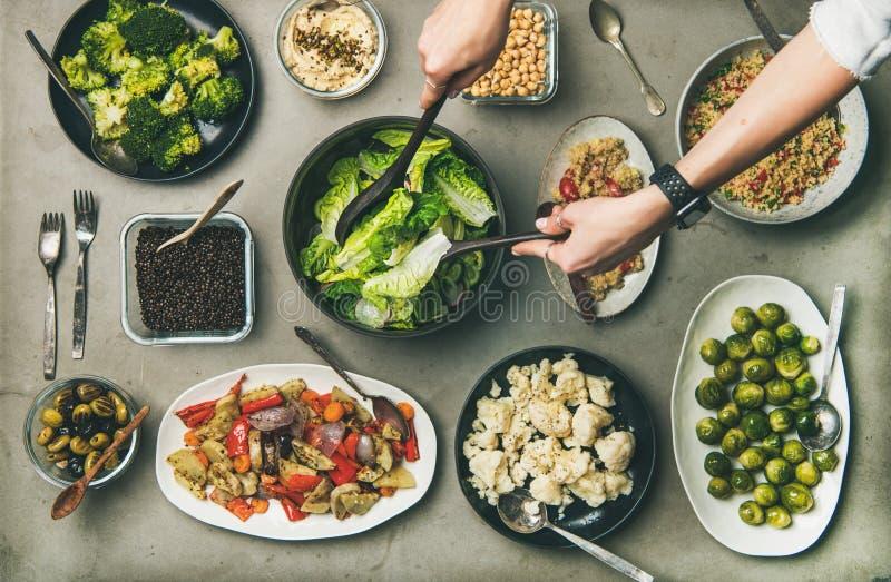 Plats végétariens sains dans les plats et des mains de la femme prenant la salade photographie stock