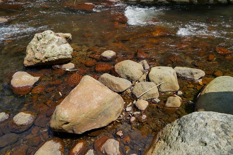 Platsen av klart sötvattenströmflöde till och med den hårda naturliga floden vaggar med laven, den lilla vågen och ljusreflexions royaltyfri foto
