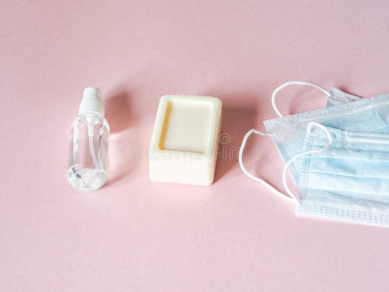 Platt personlig skyddsutrustning mot olika virus - medicinska masker, flasksaftare och tvål på rosa bakgrund arkivfoto