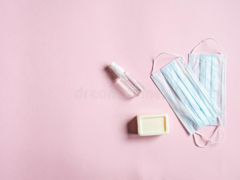 Platt personlig skyddsutrustning mot olika virus - medicinska masker, flasksaftare och tvål på rosa bakgrund royaltyfria foton