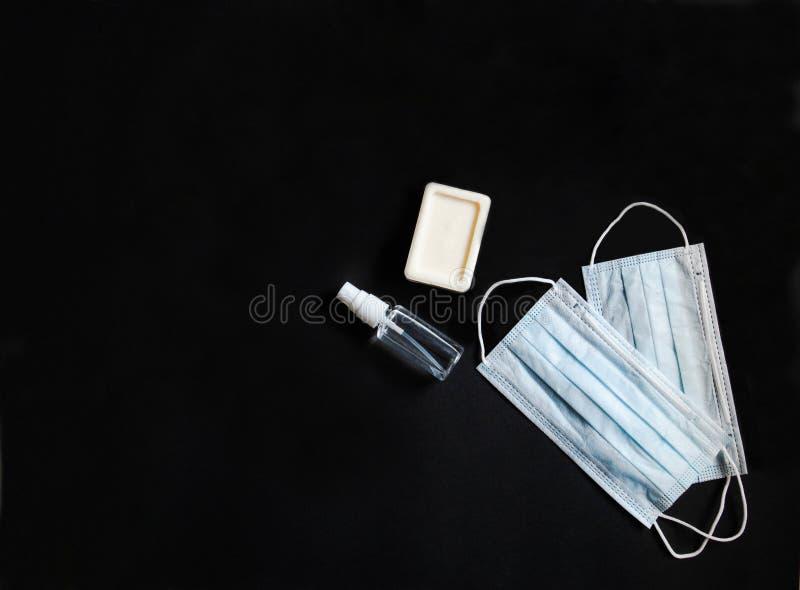 Platt personlig skyddsutrustning mot olika virus - medicinska masker, flasksaftare och tvål på svart arkivfoton