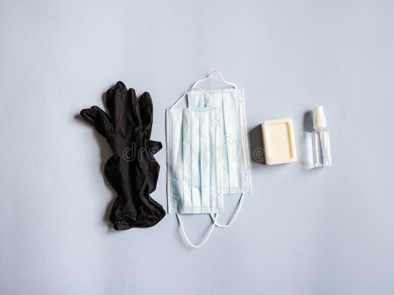 Platt personlig skyddsutrustning mot olika virus - medicinska masker, flasksaftare, tvål och svart engångsmaterial arkivbilder
