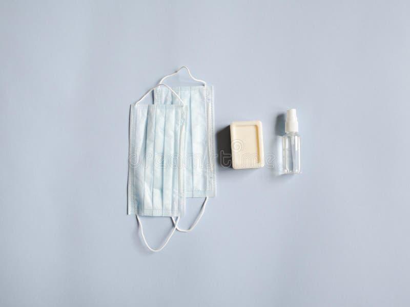Platt skyddsutrustning mot olika virus - medicinska masker, flasksaftare, tvål på blå bakgrund Kopiera royaltyfri fotografi