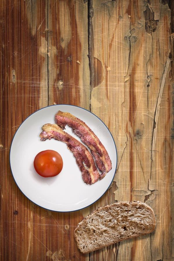 Platta av Fried Bacon Rashers med tomat- och brödskivan royaltyfri fotografi