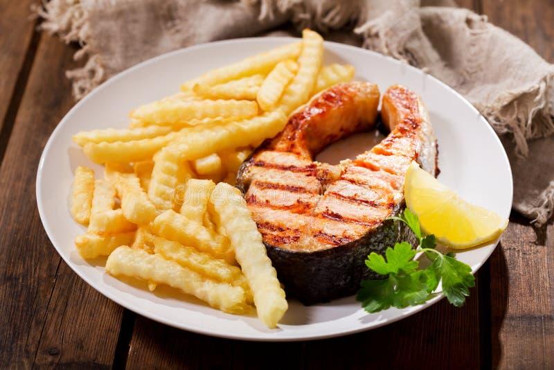 Platta av grillad laxbiff med franska småfiskar royaltyfri foto