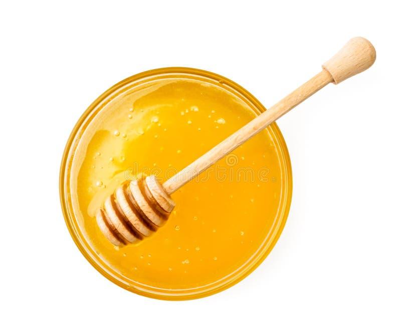 Platta av honung med en träpinne på en vit bakgrund Sikten av överkanten arkivbild