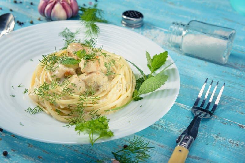 Platta av italiensk spagetti med fegt kött som står på en blå trätabell arkivbilder