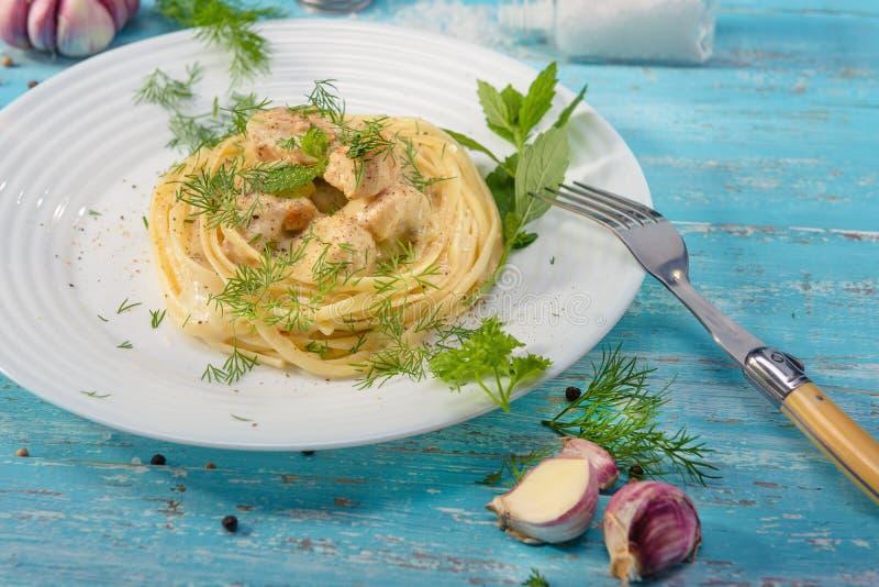 Platta av italiensk spagetti med fegt kött som står på en blå trätabell royaltyfria foton