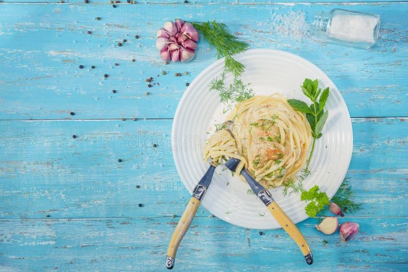Platta av italiensk spagetti med fegt kött som står på en blått royaltyfri foto