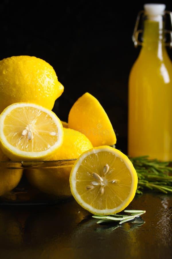 Platta av nya skivade citroner, rosmarin, flaska med citrondrinken arkivbilder