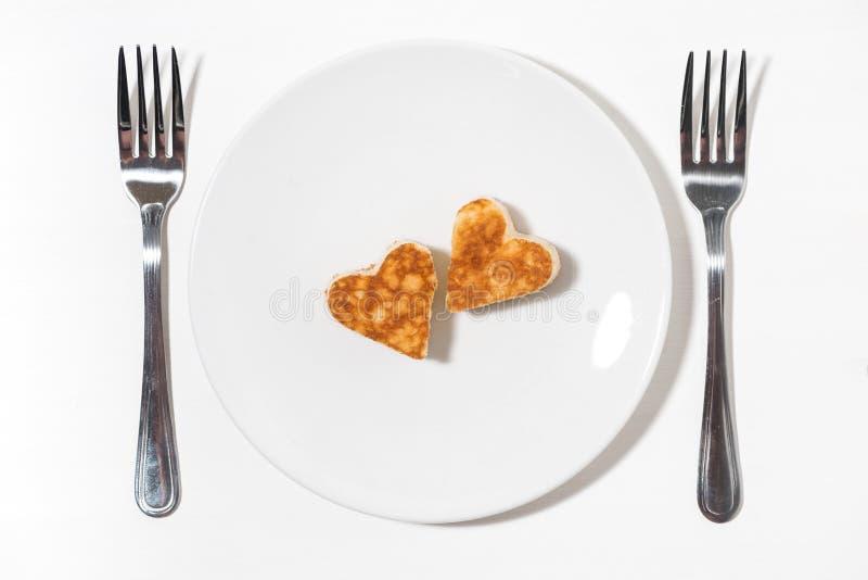 platta av pannkakor i formen av hjärta och två gafflar på vit bakgrund, bästa sikt royaltyfria bilder